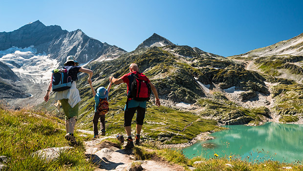 family with child hiking on holiday in austrian alps with lake a